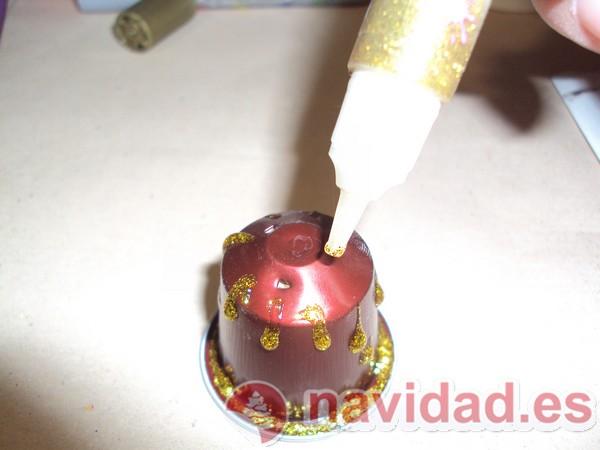Aplicando pegamento de purpurina para decorar la cápsula nespresso